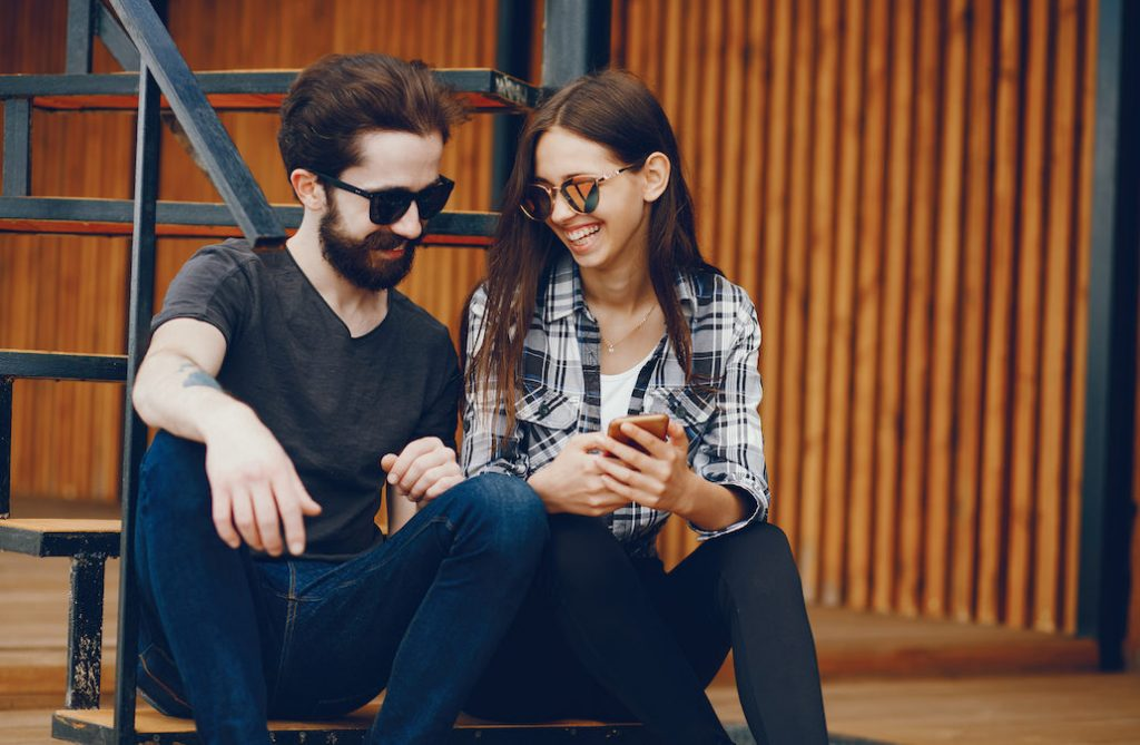 Stylish couple sitting near wall. Lovers with the phone. A pair in glasses